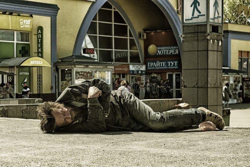 Запойный бездомный человек спит на бетоне средь бела дня стоковые фото