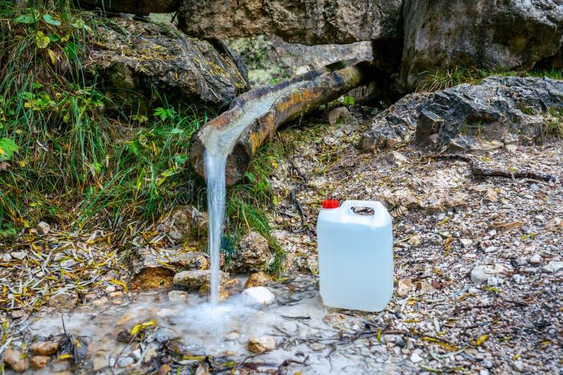 Заполнение пресной воды из горного потока в белом пластиковом контейнере для транспортировки стоковые изображения