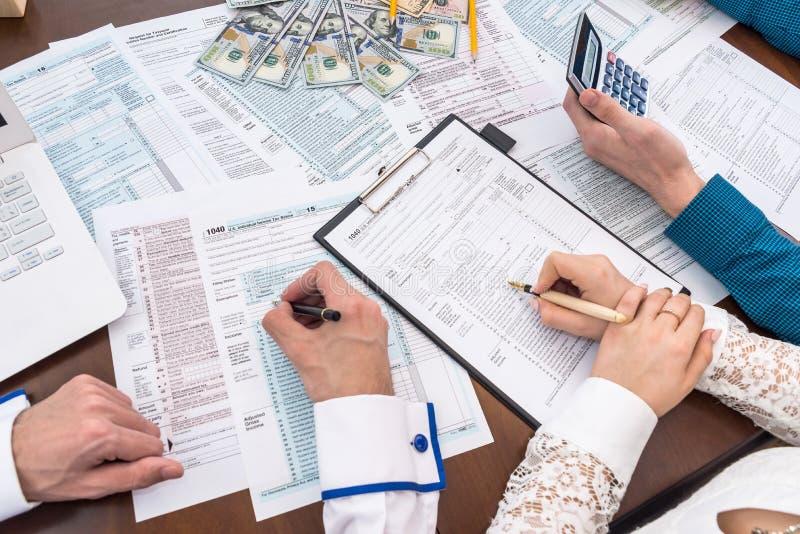 заполнение формы 1040 с помощью консультанта, налоговая компания стоковое изображение rf
