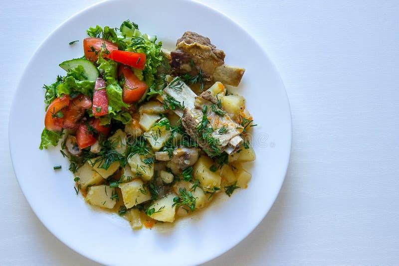 Заполненные картошки с нервюрами телятины и свежим салатом стоковые фото