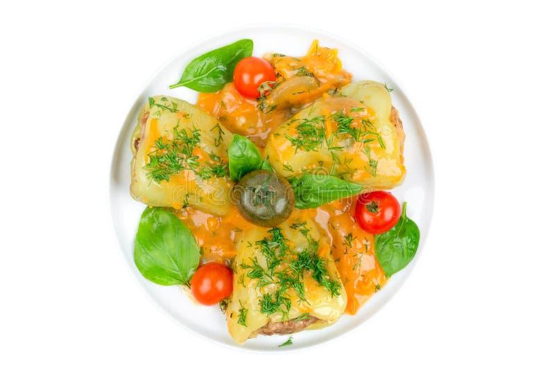 Заполненные перцы с мясом, томатами и базиликом на белой плите изолированной на белой предпосылке стоковое фото