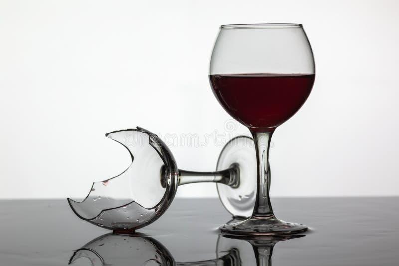 Заполненный с бокалом вина и сломленным бокалом с красным вином стоковое изображение rf