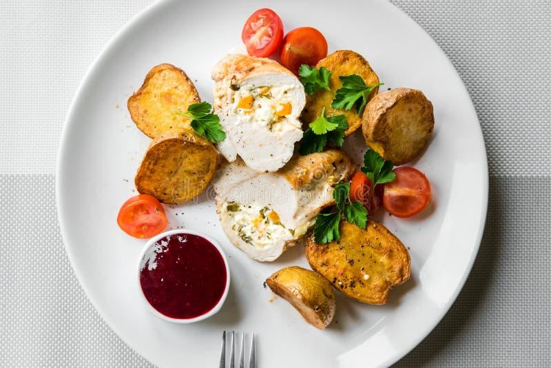 Заполненный цыпленок с печеными картофелями с томатами вишни и соусом клюквы стоковые изображения