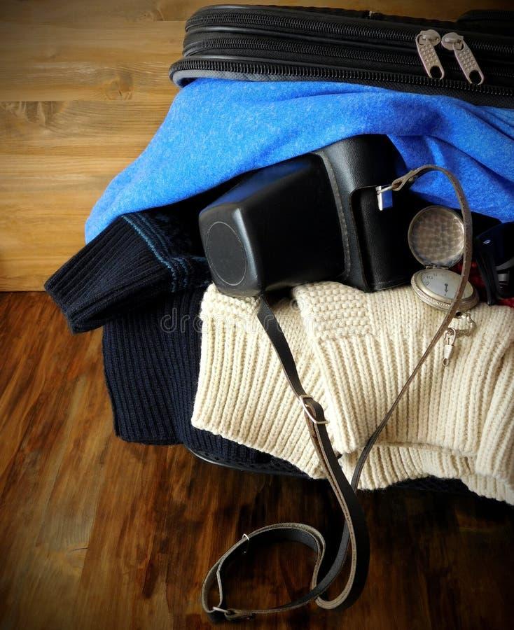 Заполненный чемодан с одеждами и старой камерой готов для отключения стоковое фото