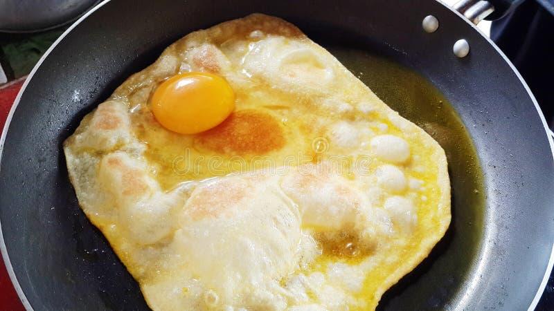 Заполните тонкий лист муки в горячей сковородке и добавьте яйцо стоковая фотография rf