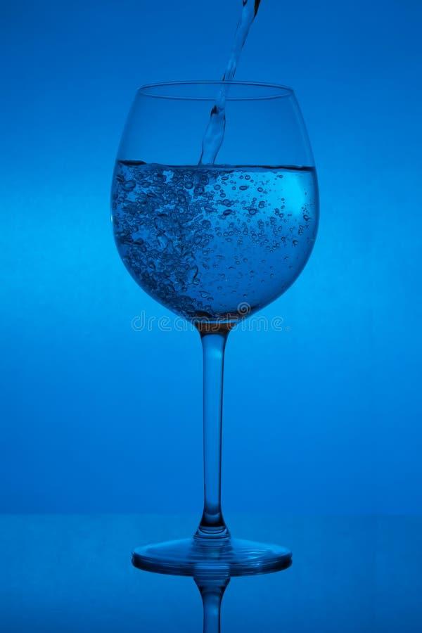 Заполнять стекло, лить рюмка на голубой предпосылке стоковые изображения rf