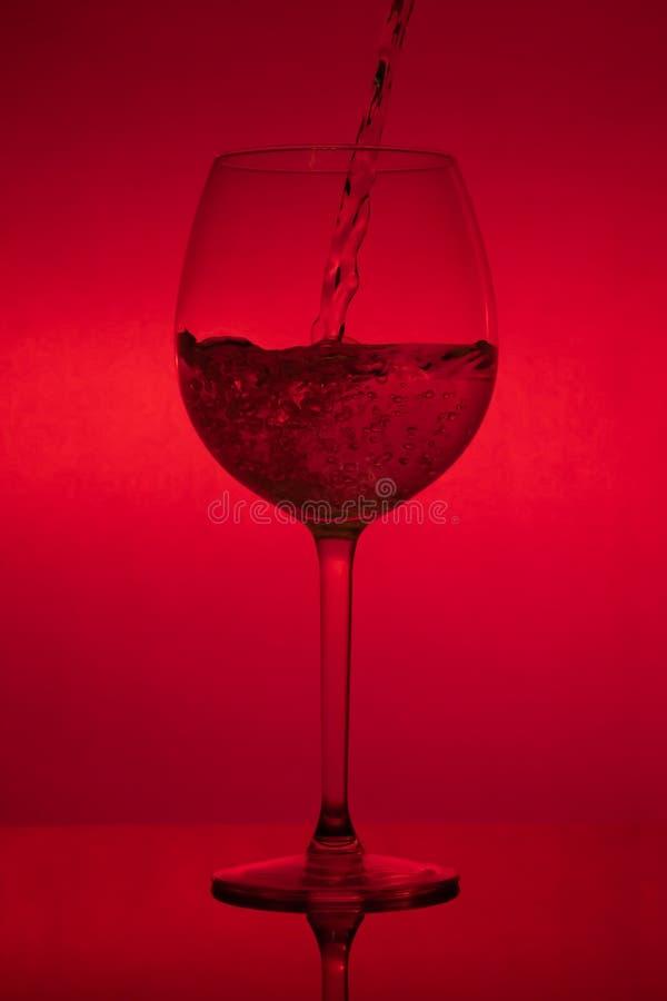 Заполнять стекло, лить рюмка на красной предпосылке стоковое изображение rf