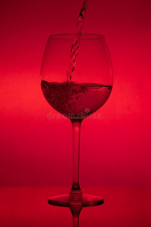 Заполнять стекло, лить рюмка на красной предпосылке стоковое фото rf