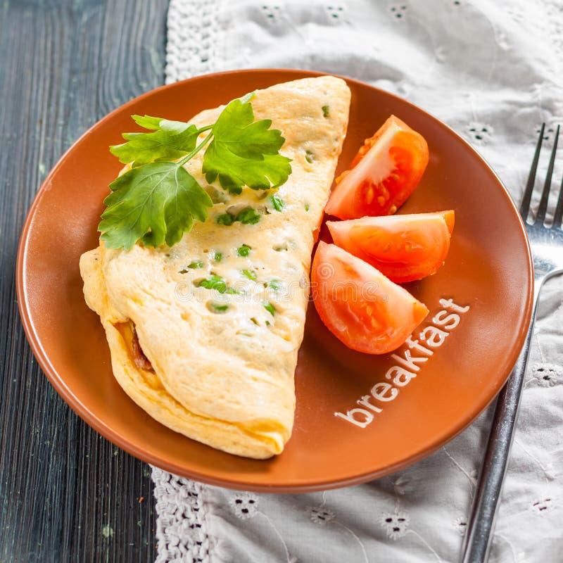 Заполненный омлет с кудрявым беконом, зелеными горохами и томатом стоковые фото