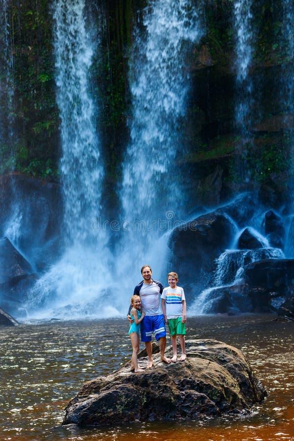 Заплывание семьи в водопаде стоковые фотографии rf