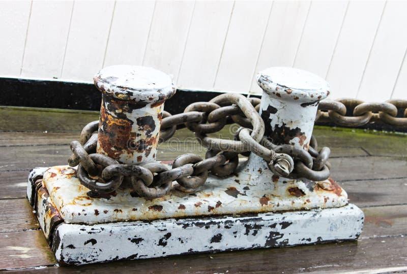 Заржаветые зажимы дока с зачаливанием приковывают прикрепленную - grunge - краску шелушась белизны - на Марине стоковые изображения