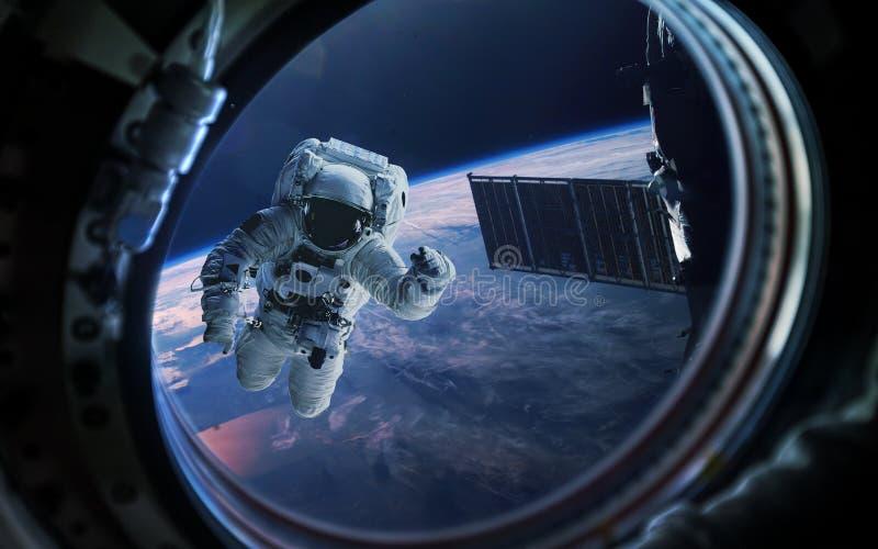 Заройте планету и астронавт в иллюминаторе окна космического корабля Элементы этого изображения поставленные NASA стоковое изображение