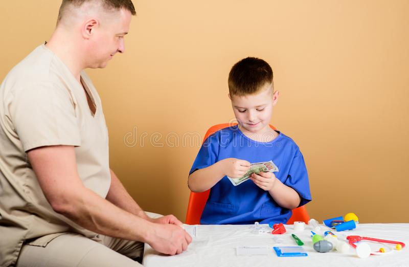 Зарплата работника больницы Ребенок мальчика милый и его доктор отца Медицинская помощь Медицинское страхование E o стоковые фото