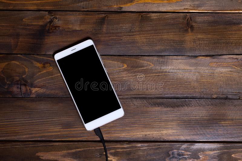 Зарядный кабель белой предпосылки мобильного телефона деревянной деревянный стоковые фото
