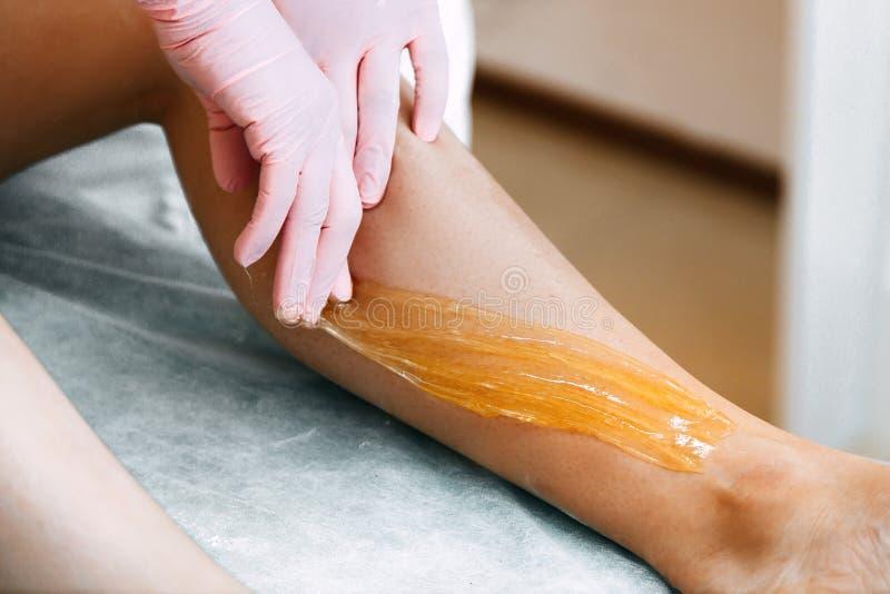 Засахаривать сахар вощия ноги в салоне красоты стоковое фото