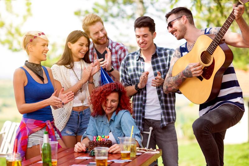 Застенчивая девушка дня рождения с друзьями которые аплодируют и играет песню дня рождения на гитаре стоковая фотография rf