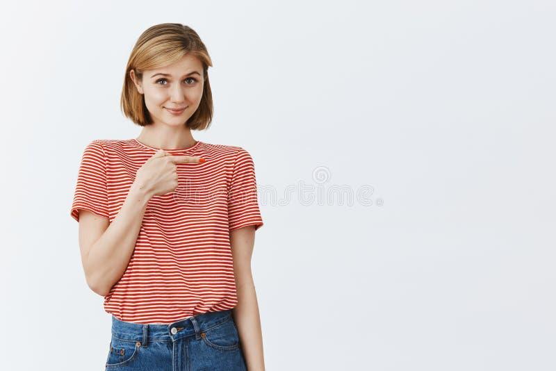 Застенчивая и трепетная милая старшая дочь стоя нестабильный над серой предпосылкой в striped футболке, указывая справедливо пока стоковое фото rf