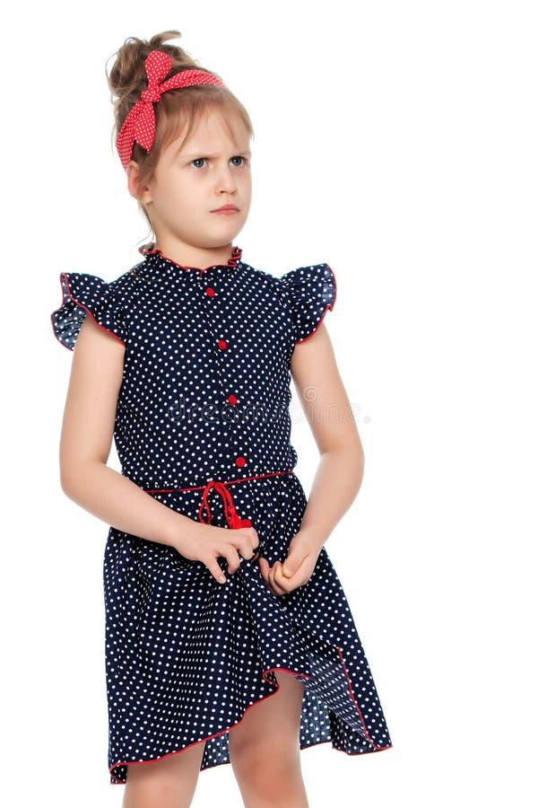 Застенчивая маленькая девочка в голубом платье стоковая фотография