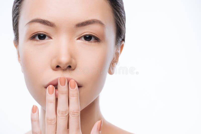 Застенчивая молодая корейская женщина касаясь ее губам в студии стоковое фото