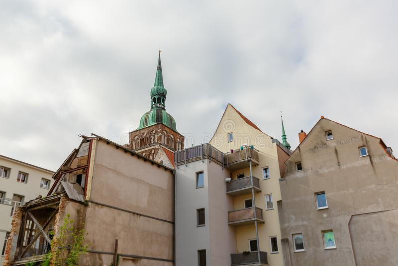 Засуженный дом с шпилем церков на заднем плане в Stralsund, Германии стоковые изображения rf