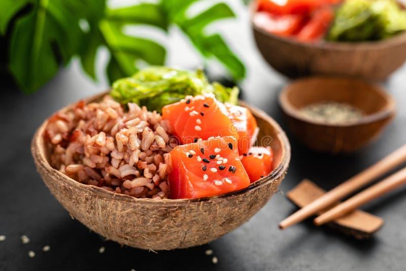 Засуньте шар с сырцовыми рыбами семг, салатом chuka и рисом в шарах кокоса на черной предпосылке стоковое изображение rf