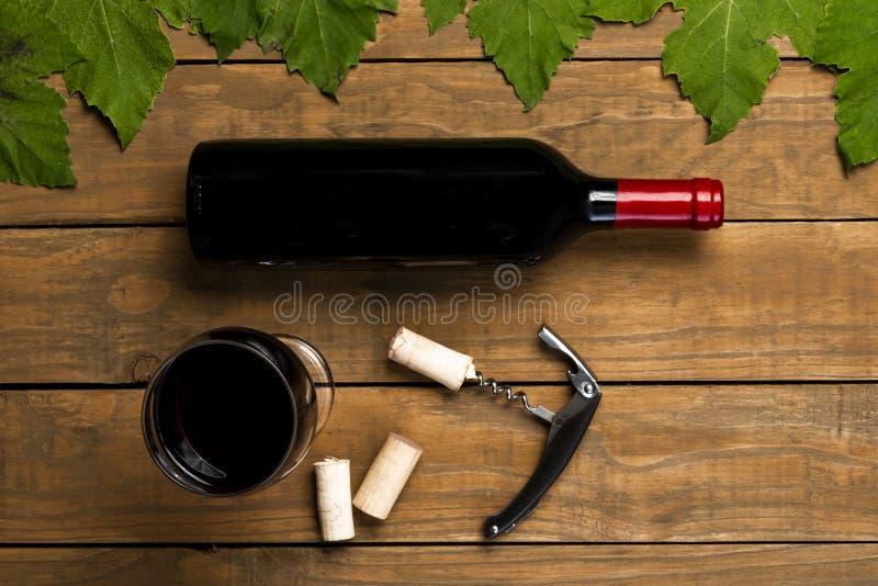 Затворы стекла консервооткрывателя бутылки вина и листья лозы на деревянной предпосылке Взгляд сверху с космосом экземпляра стоковое изображение rf