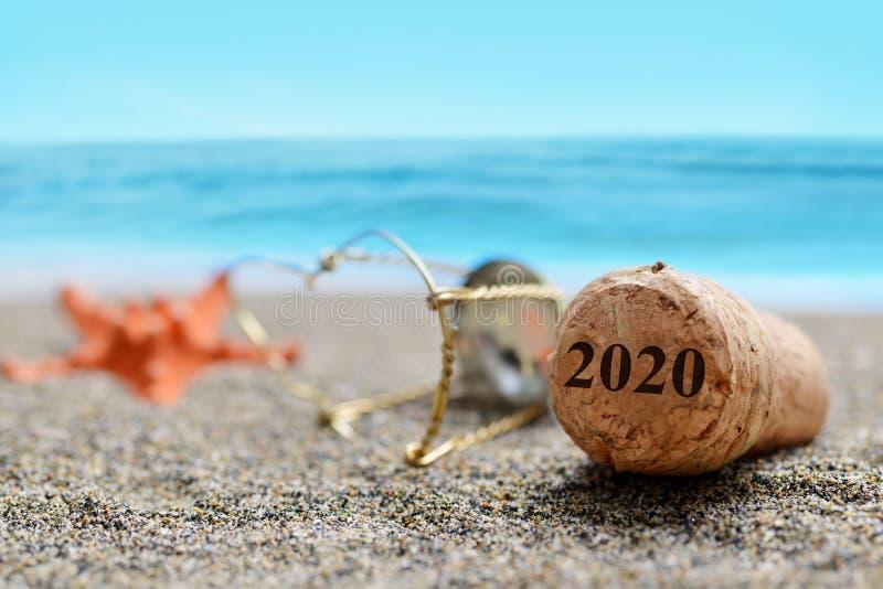Затвор пробочки шампанского с 2020 и морскими звёздами на пляже песка стоковое фото rf