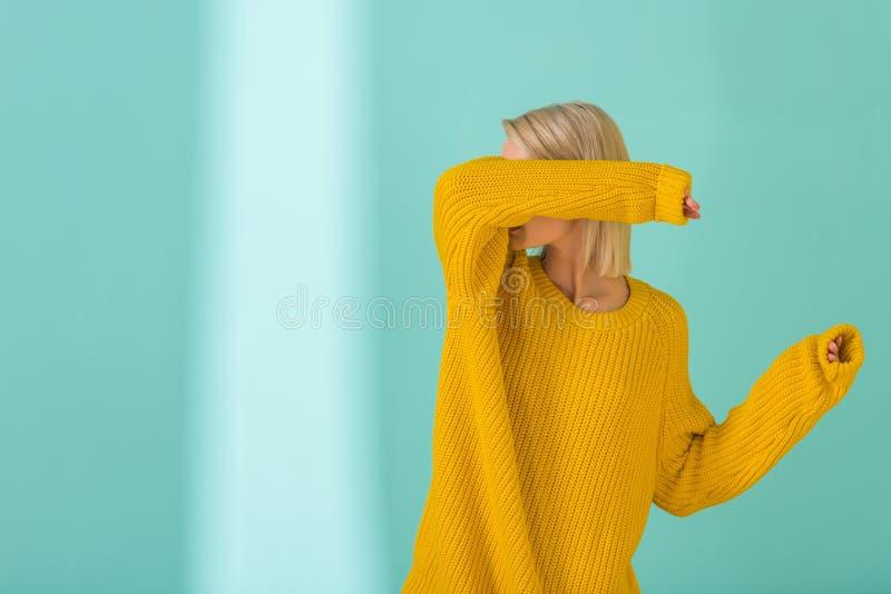 затемненный взгляд женщины в желтый представлять свитера стоковые изображения rf