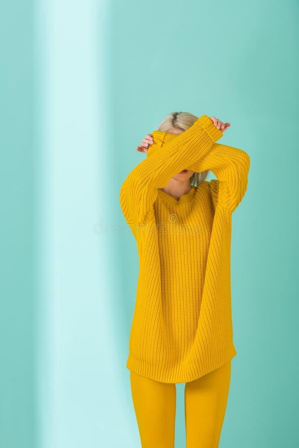 затемненный взгляд женщины в желтый представлять свитера и колготков стоковая фотография rf