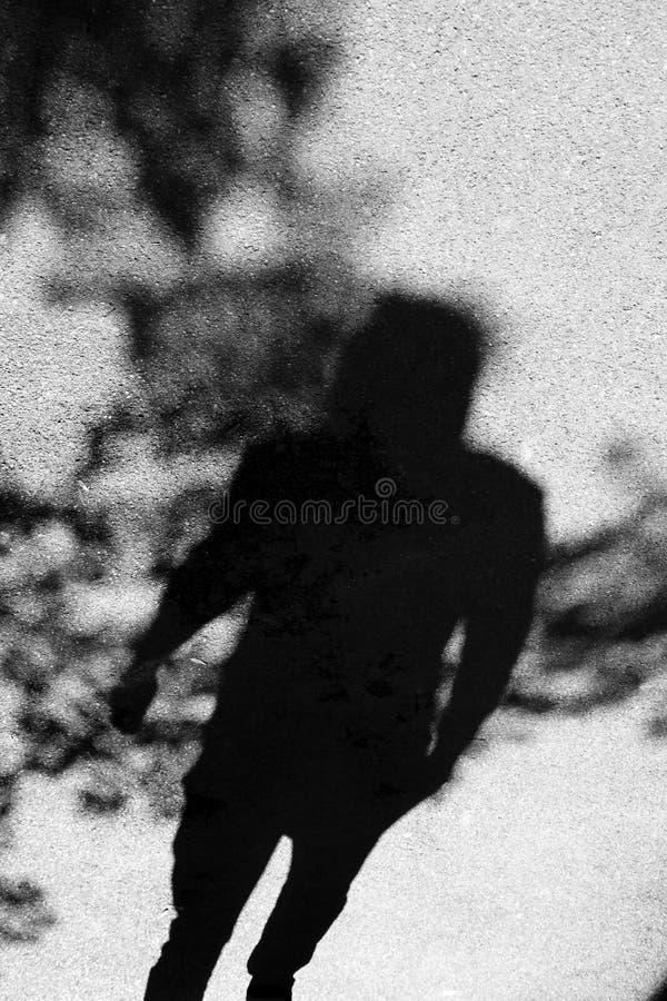 Затеняйте силуэт персоны под treetops на улице города в b стоковое фото