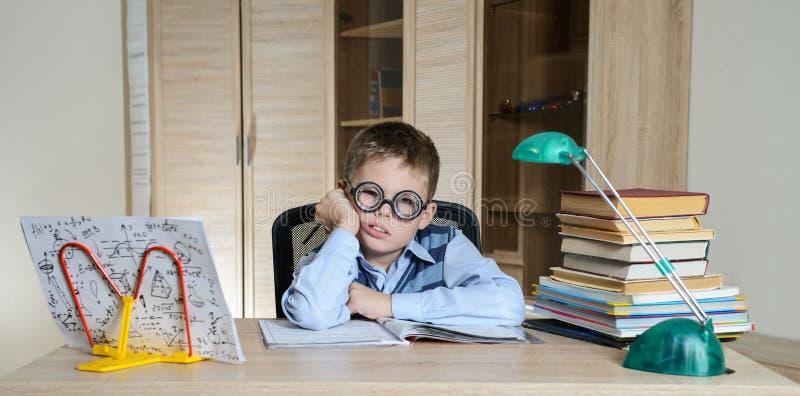 затруднения ребенка учя Утомленный мальчик делая домашнюю работу Образование стоковые фото