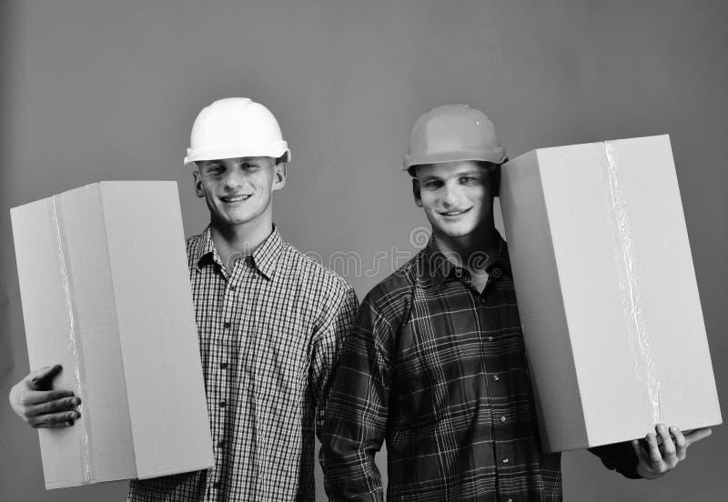Затяжелители в шлемах Близнецы с коробками владением шлемов Поставка и moving концепция стоковое изображение
