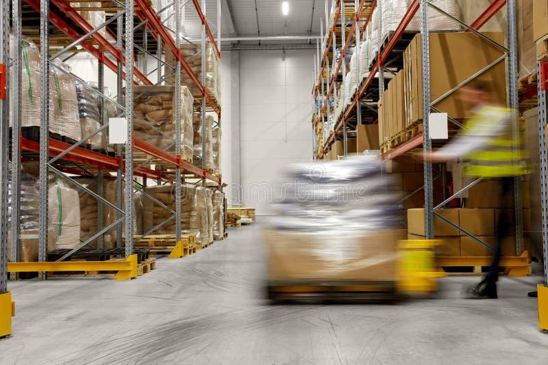 Затяжелитель нося работника с товарами на складе стоковые изображения rf