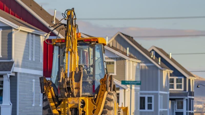 Затяжелитель ясной панорамы желтый припаркованный на дороге перед домами под конструкцией стоковое изображение