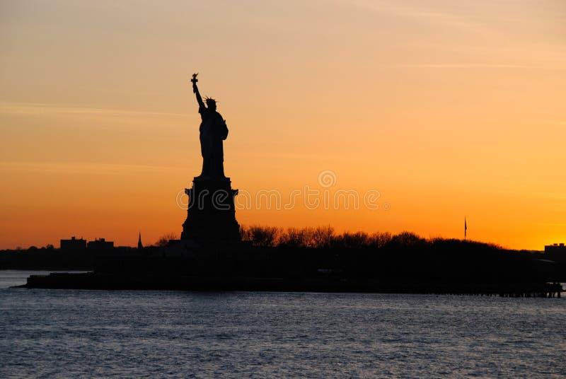 Захватывающий взгляд статуи свободы, на заходе солнца стоковые изображения rf