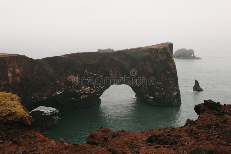 захватывающий вид на красивых скалах в океане, dyrholaey vik, reynisfjara стоковое изображение rf
