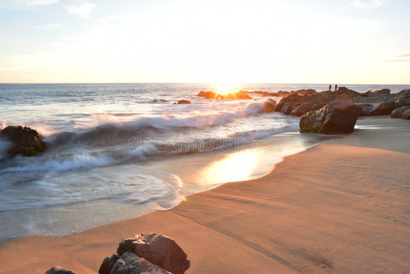 Заходящее солнце как раз на горизонте на пляже Тихоокеанского побережья в Baja, Мексике стоковое фото rf