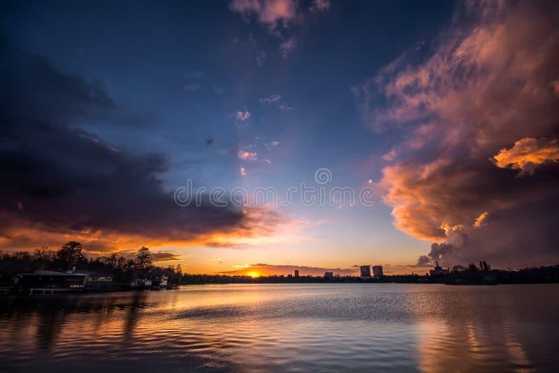 Заход солнца Бухареста с драматическими облаками над парком Herastrau стоковые фото