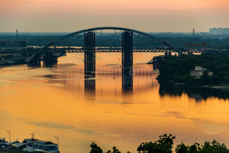 Заход солнца, взгляд ржавого незаконченного моста в Киеве, Украине Известный за свои необыкновенный дизайн и очень красивый и стоковое изображение rf
