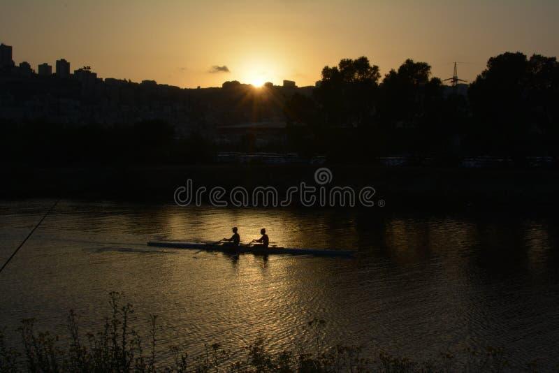 Заход солнца в анкоредже Shavit на банках реки Kishon Взгляд на Хайфе Rowers в canoeing стоковое изображение