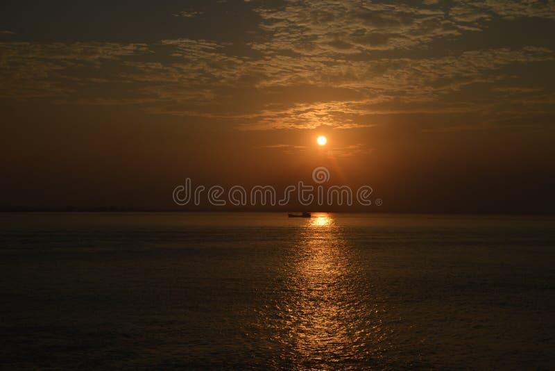 Заход солнца в Индии со шлюпкой пересекая лучи солнц стоковые фотографии rf