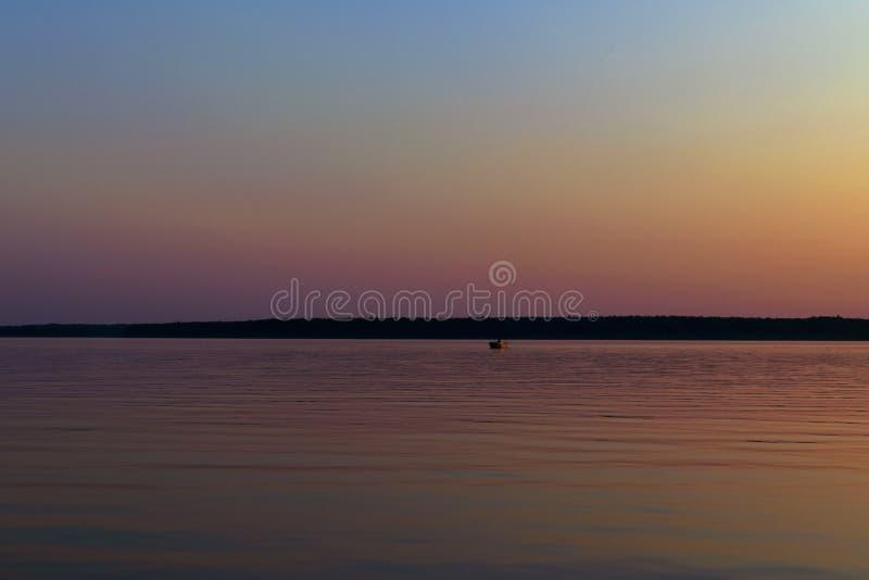 Заход солнца в море с небольшой рыбацкой лодкой на озере Изображение небольшой рыбацкой лодки с красивой предпосылкой захода солн стоковые фотографии rf