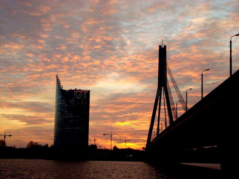 Заход солнца в небесах над рекой города стоковая фотография
