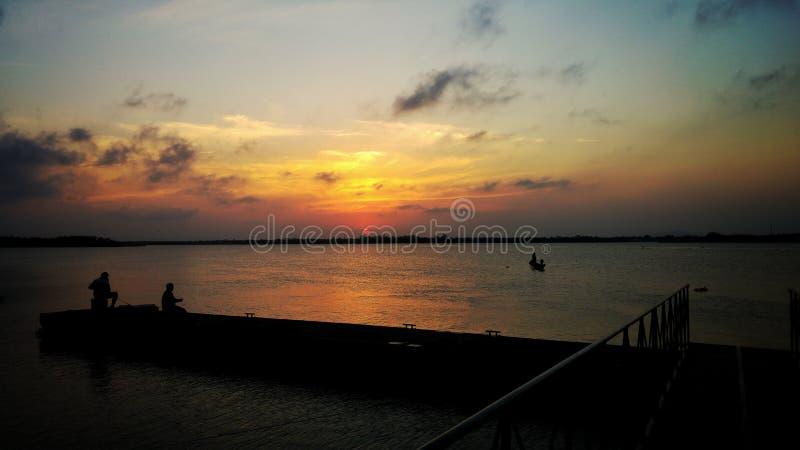 Заход солнца в океане и рыболовах стоковое фото rf