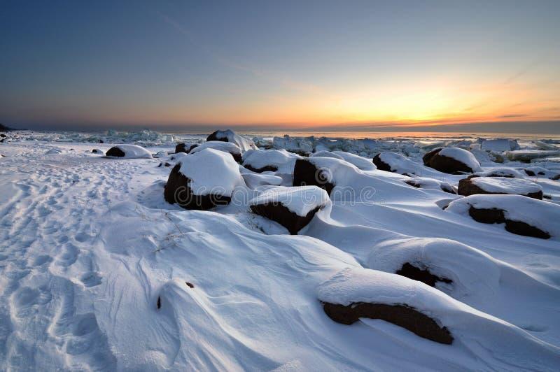 Заход солнца зимы в пляже Vidzeme каменистом стоковые фото