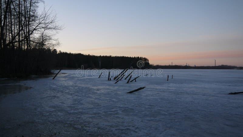 Заход солнца зимы на озере леса стоковые изображения