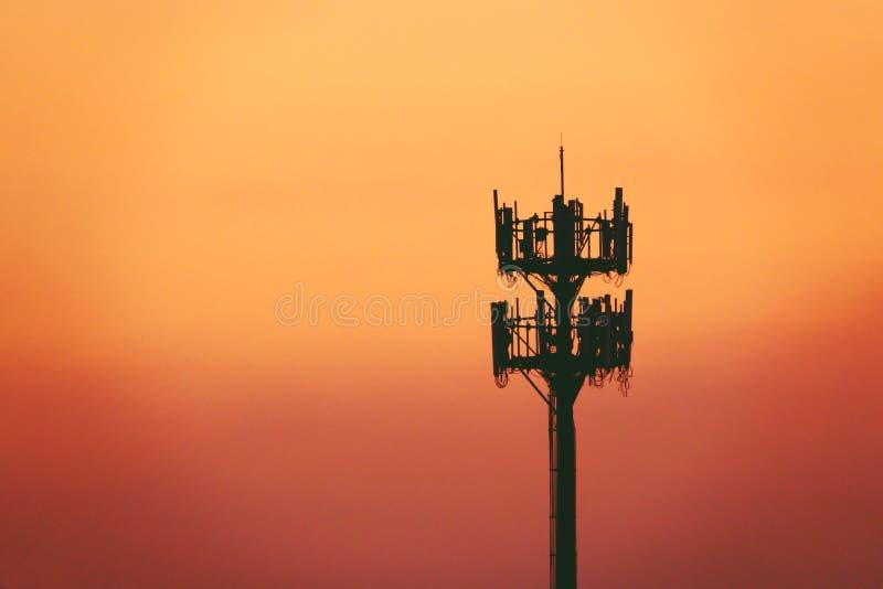 Заход солнца и высокорослый рангоут с клетчатой антенной стоковая фотография