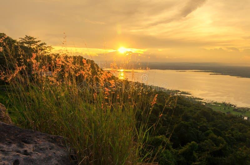 Заход солнца и горы, красивый заход солнца, солнечный свет отражают поверхность воды и трава на горах стоковые фотографии rf
