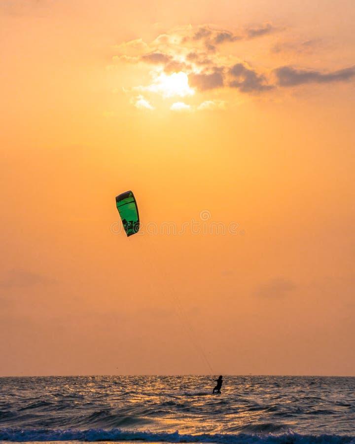 Заход солнца и змей занимаясь серфингом на пляже стоковое изображение