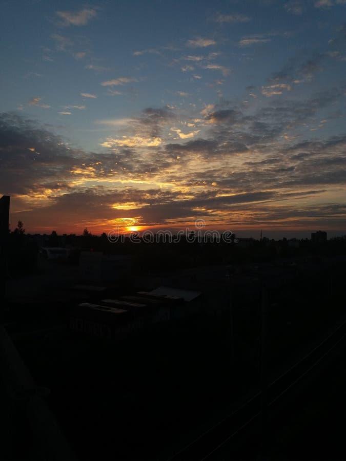 Заход солнца и облака над городом стоковая фотография